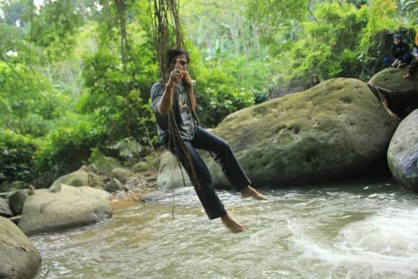 Mang Ojos sedang bergelantungan di sebuah akar pohon tua di Dusun Cipaga